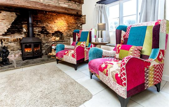 Comfortable chairs next to log fire